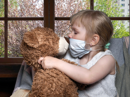 Little kid in a medical mask kissing toy bear. Outside, the trees are blooming. Conceptually about allergies, colds and Ecology