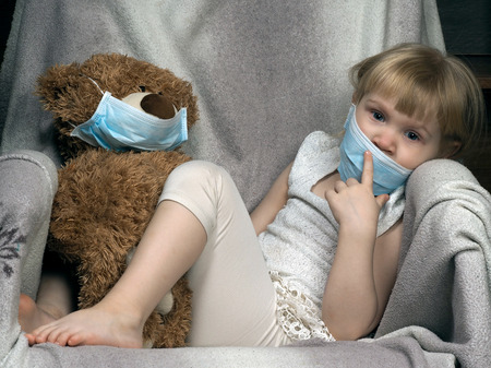 medical distribution: Small child with a toy bear cub in a medical mask. The girl is sad. Concept - an allergy to dust, wool, asthma. risk of infection, the viruses.