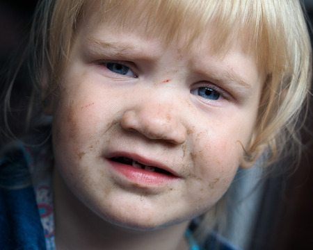 Portrait of a dirty child. The child in the mud smeared face
