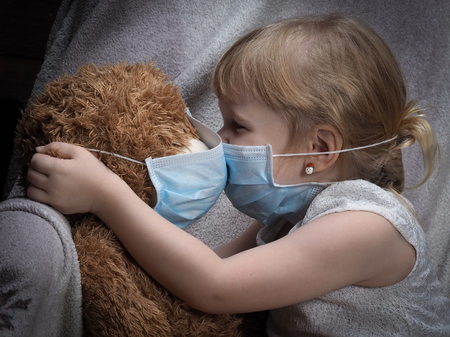 Kiss through the medical mask. A small child kisses teddy bear. Toy and children in masks.