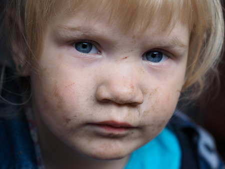 unhappiness: Portrait of a dirty child. The child in the mud smeared face