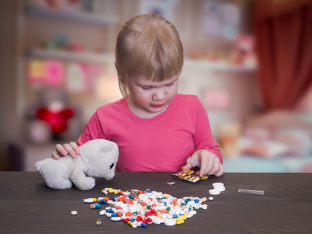 child plays with pills. Girl feeds pill capsule toy - polar bear cub. Danger game with pills. Bad game. The risk of poisoning