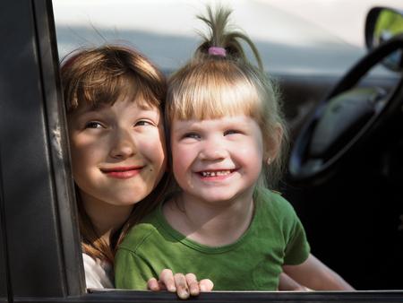 grimy: Children look out the car window. Children grimy, satisfied. Portrait of two girls. Concept - travel with children in the car. Childrens holiday, happy children. Stock Photo