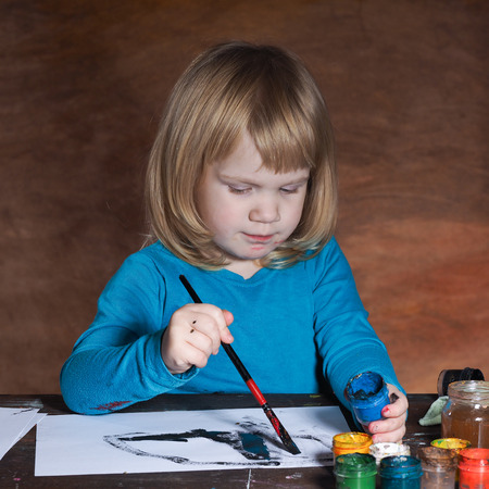engaging: Child draws with black paint and a brush on a piece of paper. Red background. The girl blonde hair. Girl keen, it is interesting lesson Stock Photo