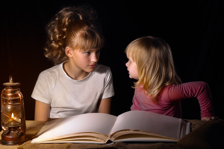 bedtime story: Two sisters tell each other scary stories at night. Open book, vintage lamp (kerosene). Black background. A family. Girls sister, older and one younger. Babies interesting and scary. Bedtime Story