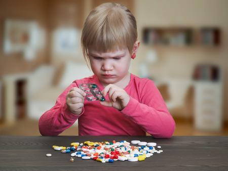 child plays with pills. Girl gets pill capsule from the blister. Danger game with medication, pills. Risk of poisoning baby