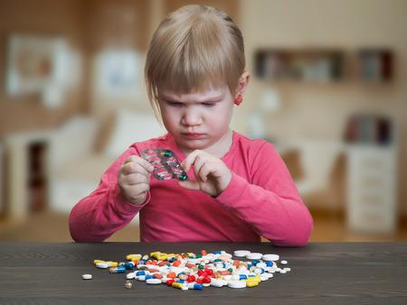L'enfant joue avec des pilules. Fille reçoit une pilule de la plaquette. Jeu de danger avec des médicaments, des pilules. Risque d'empoisonnement bébé Banque d'images - 65749581