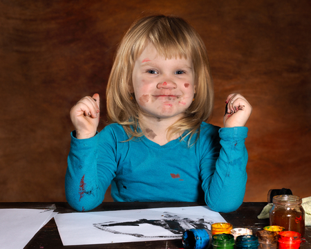 grubby: Child draws. The girl soiled in a paint. Funny little girl and grubby. Paint stains on the face. Bright brown background