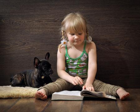 Little girl reading a book sitting on the floor. Nearby lies a dog. Girl in jeans and barefoot. Blond hair, pigtails. Book great. Read interesting. Dog black French bulldog