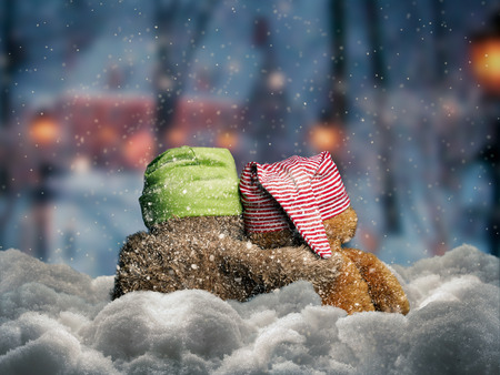 Teddy bears in caps sitting in the snow under the falling snow. Toys tenderly embrace each other