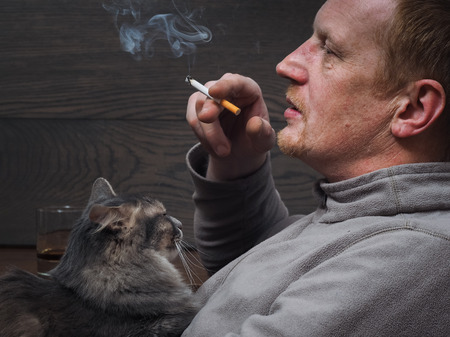 Man resting. On lap cat, holding a cigarette, on a table a glass with alcohol. Men's joy or bad habits Standard-Bild