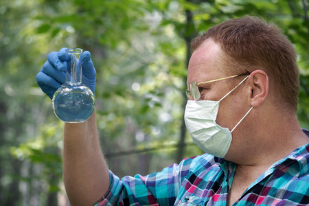 The man with glasses and a mask holding a retort with a transparent liquid. Concept - the study of water quality, chemical analysis, environment, ecology Stock Photo