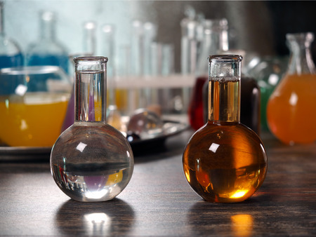 The flasks with different liquids - clear and dark. Laboratory glassware with colorful liquids on the table