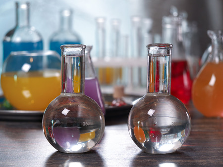 Flasks with clear water. Laboratory glassware with colorful liquids on the table Stock Photo