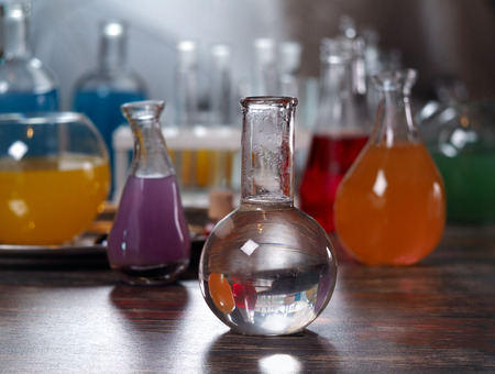balanza de laboratorio: The bulb with clear water. Laboratory glassware with colorful liquids on the table