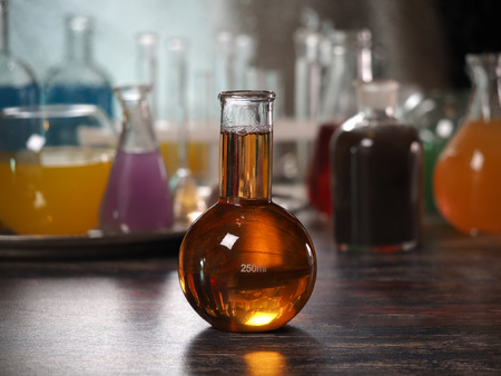 Retort with amber liquid. Laboratory glassware with colorful liquids on the table