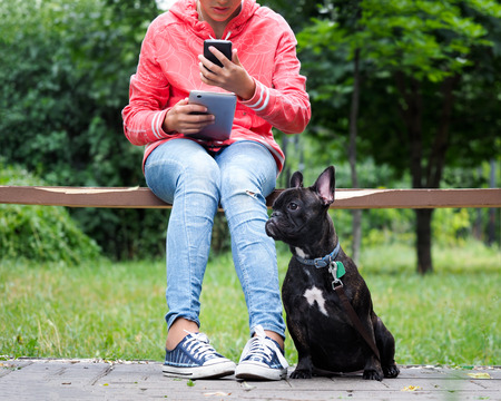 teenager with a phone and a tablet computer in hands sits on a bench in the Park. Next to the dog