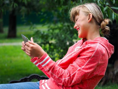 Cheerful, joyful teen girl with a gadget in hand