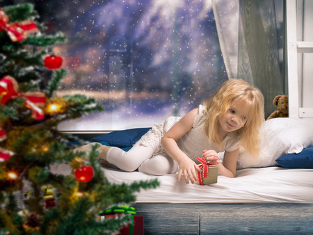 small child on the bed with a gift. Window, snow, a Christmas tree. Waking up in the morning, the first day of the new year
