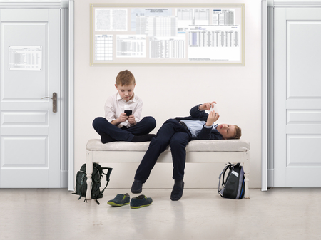 absenteeism: Boys play phones in a public institution - a school or clinic Stock Photo