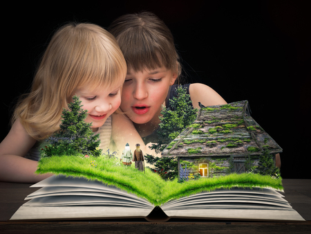 The children delighted in watching a fairy tale on the pages of an open book. Tale characters - the old man and old woman. Rustic old house, a forest glade with flowers. Stock Photo