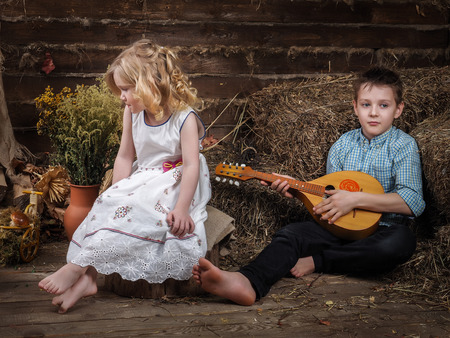 Children in the hayloft. The boy with the mandolin. The teenager plays a musical instrument. Beautiful girl in a white dress. Old village house