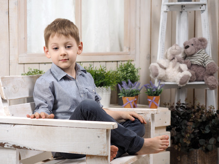 Pensive little boy. Bright childrens room. Portrait of a child