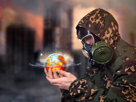 Man in gas mask looking at a globe in his hands. The planet glows, continents in flames. A man in uniform