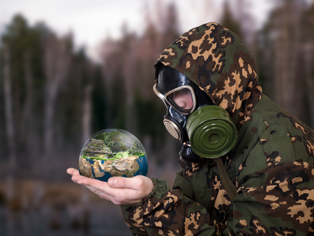 Man in a military uniform and a gas mask holds in his hands the globe. Stock Photo