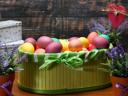 lavender coloured: Many colored Easter eggs in a basket. Flowers lavender