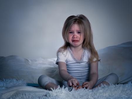 Le bébé est en train de pleurer. Une petite fille au lit pour la nuit Banque d'images - 73766720