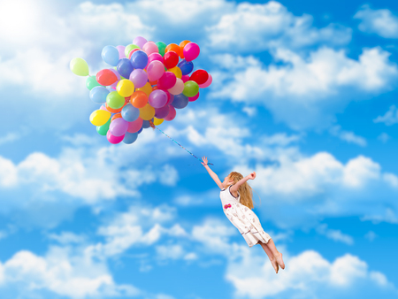Child flies on the balloons. Blue sky, clouds. A little girl in a white dress 스톡 콘텐츠