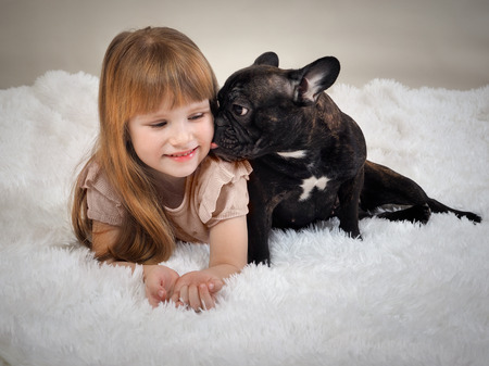 The dogs licking the baby. Redhead little girl and a pet dog - black French bulldog