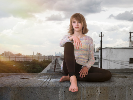 Teenage girl sitting high on the roof. The city, the suns rays