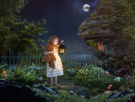 The little girl in the night in a beautiful magical forest. Girl holding an antique lantern and a toy bear. Childrens fairy tale
