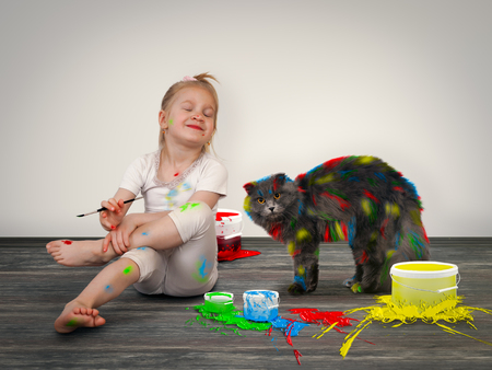 Happy child painted cat with colored inks. Girl and pet. Creativity and creative development in children Stock Photo