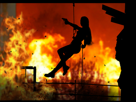 The raging flames of fire, the silhouette of a girl soldier with a gun. 版權商用圖片
