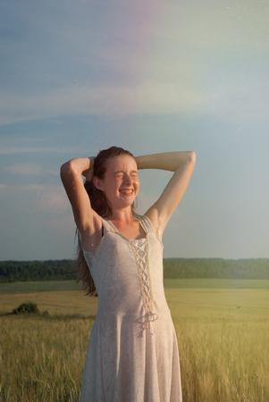 フィールドで美しい夏の女の子。太陽の光や雨。笑って幸せな若い女