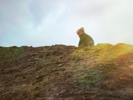 小さな女の子は、砂の背の高い山を登っていきます。太陽の光線