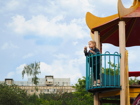 Child blow bubbles with height. High Playground, sky, house