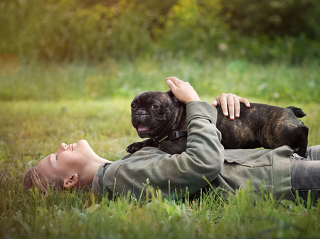 french ethnicity: Girl lying in the grass hugging a dog. Nature, green grass, beautiful Stock Photo