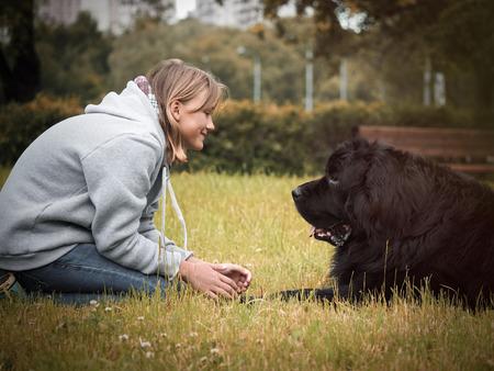 Teen girl avec un énorme chien dans le parc Banque d'images - 81163038