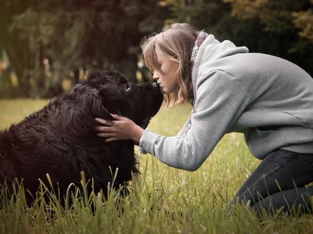 newfoundland: A teenage girl and a huge dog. Kiss of man and Newfoundland. Nature Park Stock Photo