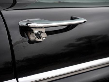Beautiful chrome door handle on an old black car