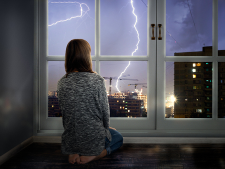The girl looks through the window at the lightning. Thunderstorm in the city