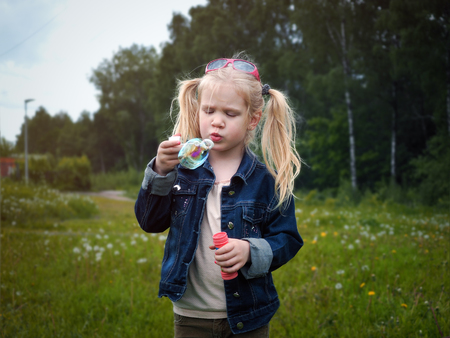 Girl inflates soap bubble. Portrait of a child. Long blonde hair, beautiful face. Nature, field, green, grass, forest Banco de Imagens