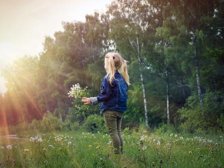 フィールドの花の花束を持つ少女。子供は太陽の光を見てください。 写真素材