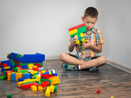 boy plays in the construction. Colorful toy designer, a lot of details