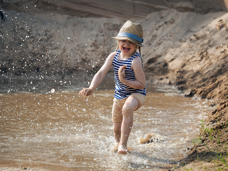 Incredibly happy child running fast on the water. Sand pit, muddy water in a puddle, much of the spill