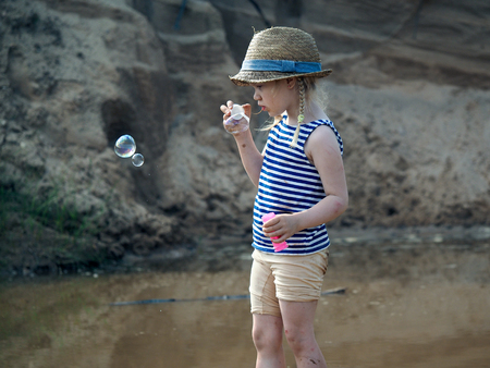 Little girl in bonnet inflates soap bubbles. The child is dirty Banco de Imagens